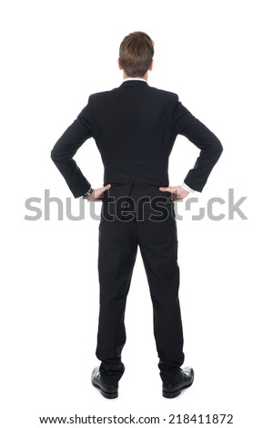 Full length rear view of confident businessman standing with hands on hips over white background - stock photo
