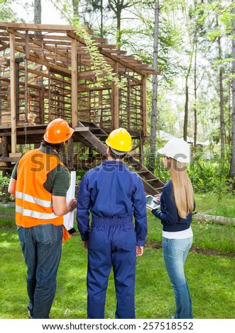 Full length rear view of male and female architects looking at incomplete wooden cabin - stock photo