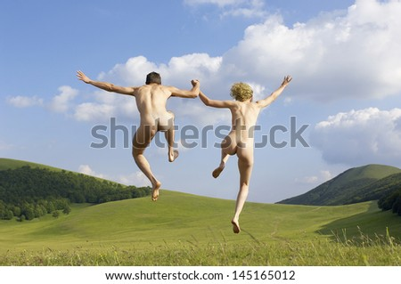 Full length rear view of naked young couple holding hands while jumping in park - stock photo