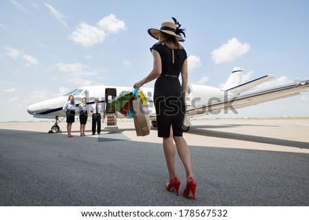 Full length rear view of woman carrying shopping bags while walking towards private jet at airport terminal - stock photo