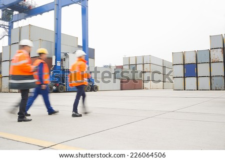 Full-length rear view of workers walking in shipping yard - stock photo