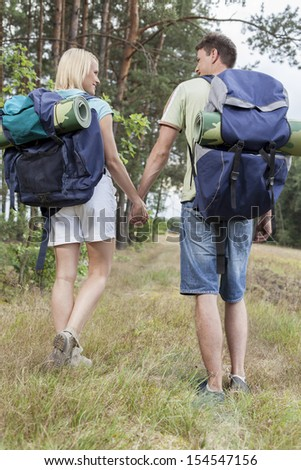 Full length rear view of young backpackers holding hands in countryside