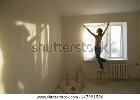 Full length rear view of young woman fitting curtain in new apartment - stock photo