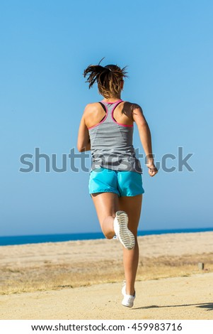 Full length rear view of young woman running at sea front.
