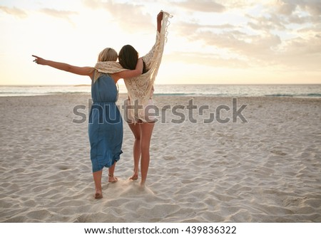 Full length rear view shot of two young women walking on the beach with their hands raised. Female friends having fun on the sea shore.