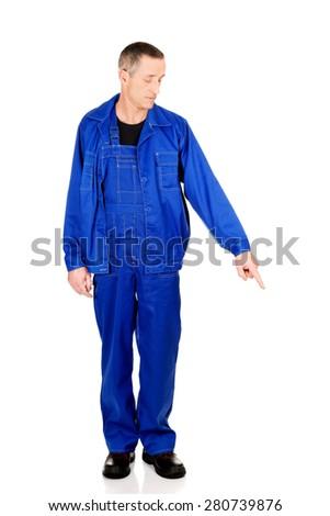 Full length repairman pointing down. - stock photo