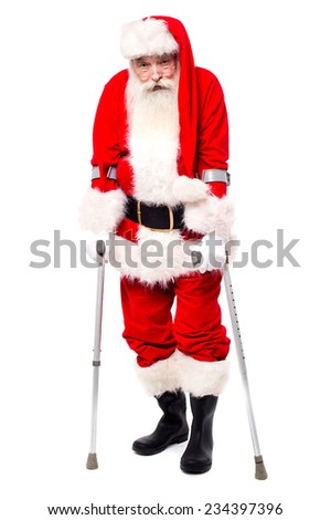 Full length santa claus standing with crutches  - stock photo