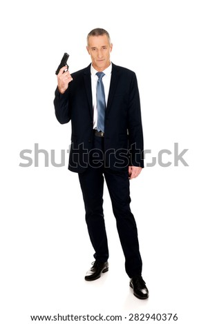 Full length serious mafia agent with handgun. - stock photo