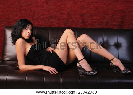 Full length shot of a beautiful Hispanic girl wearing a black dress laying on a brown leather sofa. - stock photo