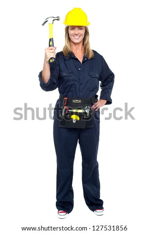 Full length shot of a business architect displaying hammer to the camera.