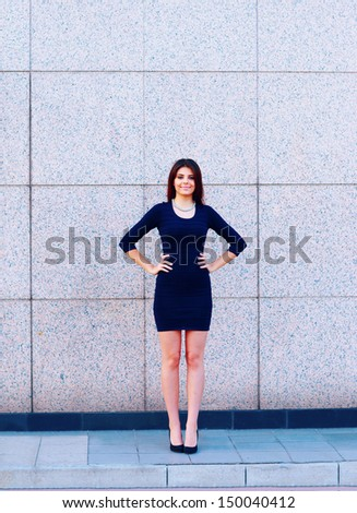 full-length shot of a happy beautiful businesswoman in formal dress outdoors - stock photo