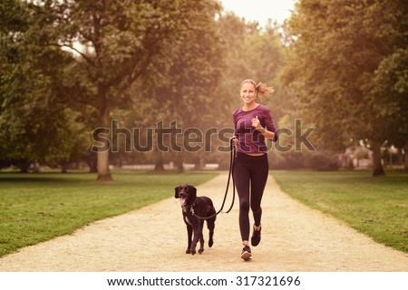 Full length Shot of a Healthy Young Woman Jogging in the Park with her Black Pet Dog - stock photo