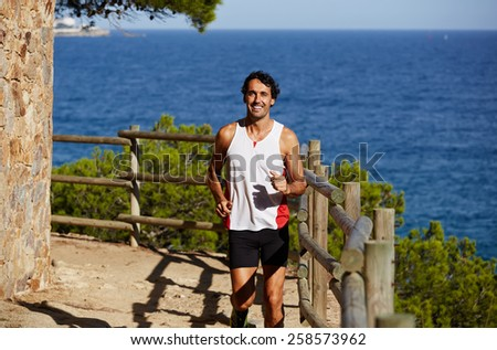 Full length shot of a smiling mature man running on the beach with beautiful sea on background, jogging athlete over mountain trail on high altitude - stock photo