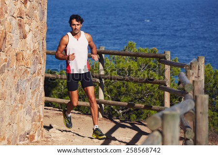 Full length shot of a sporty mature man running on the beach with beautiful sea on background - stock photo