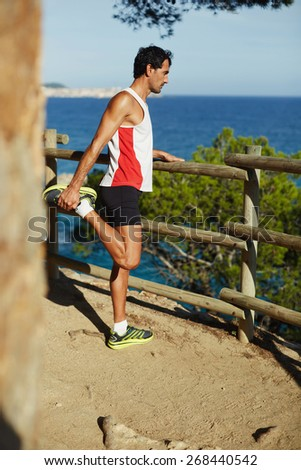 Full length shot of an attractive mature man stretching his hamstrings before the jog along coastline at sunny evening  - stock photo