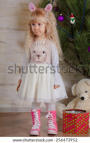 Full Length Shot of Blond Little Girl, in Trendy Outfit, Showing Sad Face While Standing Near thee Christmas Tree. - stock photo