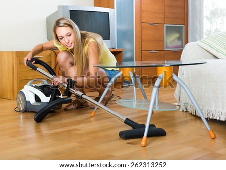 Full length shot of blonde woman cleaning with vacuum cleaner at home - stock photo