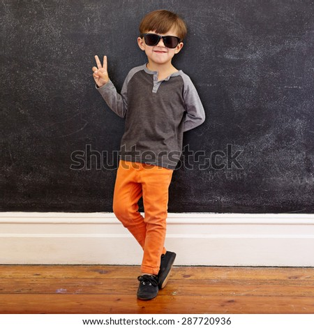 Full length shot of cool little boy wearing sunglasses gesturing victory sign. Young school boy in casuals showing peace symbol while leaning on a black wall at home. - stock photo