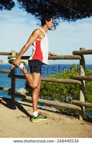 Full length shot of mature man stretching his legs before a run outdoors at sunny day, athletic man enjoy the view while doing stretch exercise before a jog  - stock photo