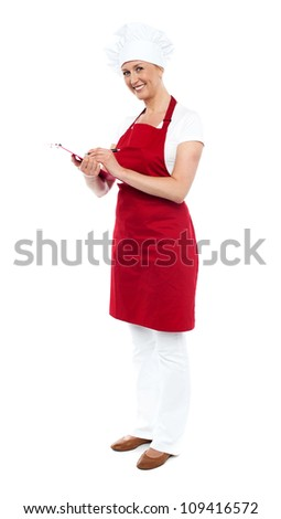 Full length shot of pretty smiling female cook writing recipe on notepad - stock photo