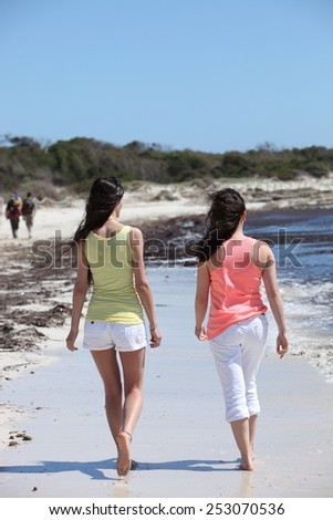 Full Length Shot of Rear View of Women Walking at the Beach on a Tropical Climate During Summer. - stock photo