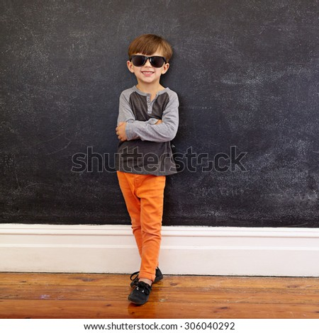 Full length shot of stylish little boy standing in front of the blackboard with his arms crossed and smiling. Caucasian kid wearing sunglasses looking at camera with a sweet smile on his face. - stock photo