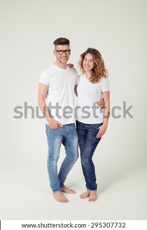 Full Length Shot of Sweet Young Couple in Casual White Shirt with Copy Space and Blue Jeans Smiling at the Camera, Isolated on White Background. - stock photo