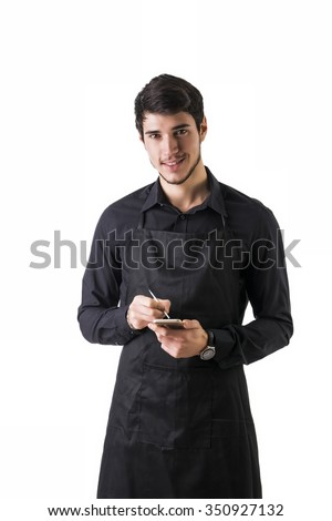 Full length shot of young chef or waiter posing, wearing black apron and shirt, writing order electronic device, isolated on white background - stock photo
