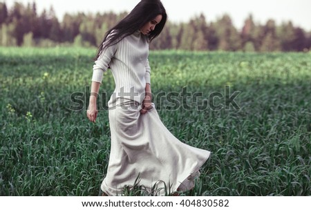Full length side fashion portrait of young beautiful brunette girl in white dress walking in grass. Long black hair. Outdoor. Summer. - stock photo