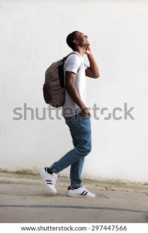 Full length side portrait of a cheerful male student walking and talking on cell phone - stock photo