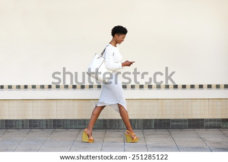 Full length side portrait of a young woman walking and sending text message on cell phone  - stock photo