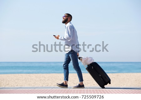 Full length side portrait of happy traveler walking by sea with luggage and cellphone