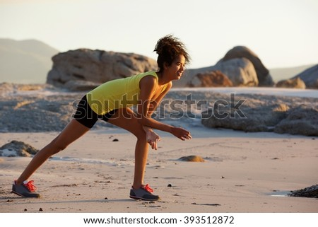 Full length side portrait of young woman enjoying exercise on the beach - stock photo