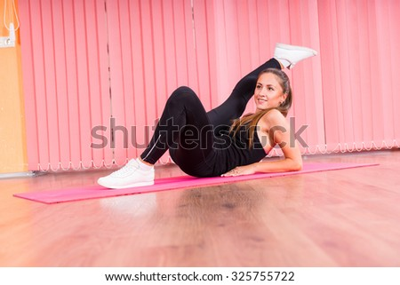 Full Length Side Profile of Young Brunette Female Dancer Reclining on Pink Floor Mat with Leg Extended Above Head in Colorful Dance Studio - stock photo