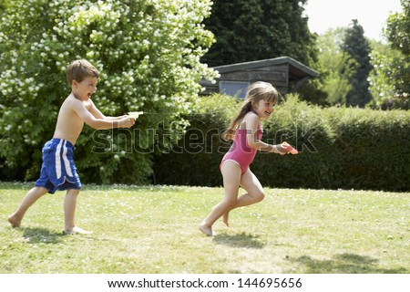 Full length side view of a boy shooting girl with water pistol in the backyard - stock photo