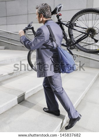 Full length side view of a businessman carrying bicycle up steps - stock photo