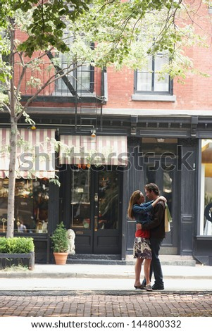 Full length side view of a couple embracing on street - stock photo