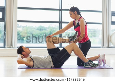 Full length side view of a female trainer assisting young man with his exercises in the bright gym