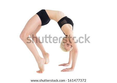Full length side view of a fit young woman doing the wheel pose over white background