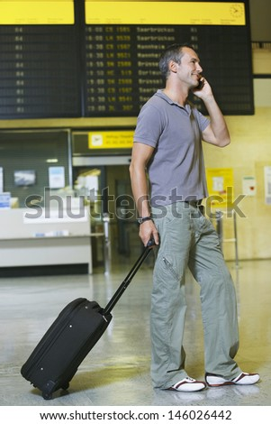 Full length side view of a male traveler using mobile phone in front of flight status board in airport - stock photo