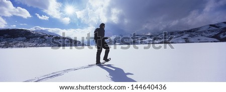 Full length side view of a man hiking through snow against cloudy sky - stock photo