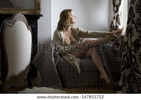 Full length side view of a semi dressed woman sitting in chair by window at home - stock photo