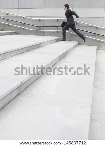 Full length side view of a young businessman running up steps outdoors - stock photo