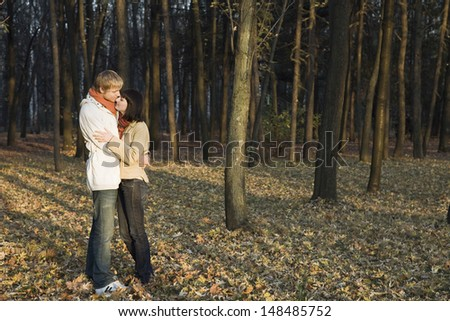 Full length side view of a young couple embracing in forest - stock photo