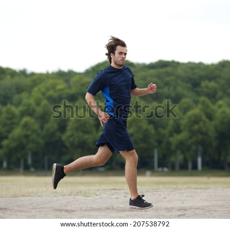 Full length side view of a young man running outside