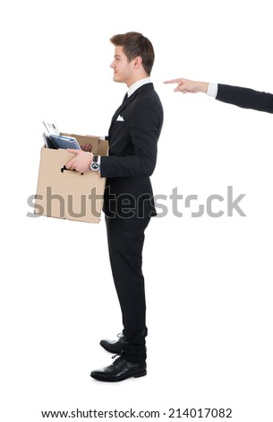 Full length side view of businessman carrying cardboard box with hand pointing at him against white background - stock photo