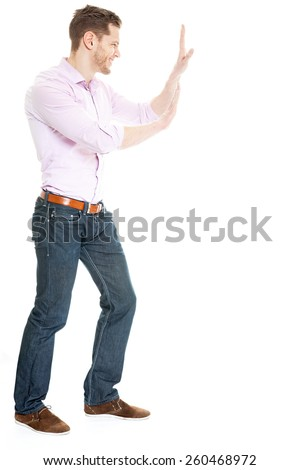 Full length side view of businessman pushing invisible wall against white background - stock photo