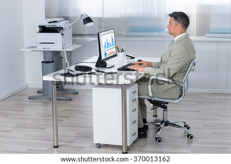 Full length side view of businessman using computer at desk in office - stock photo