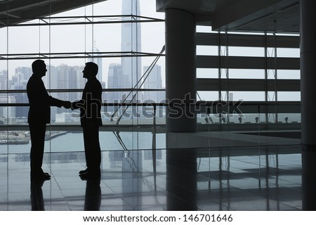 Full length side view of businessmen shaking hands in airport terminal - stock photo