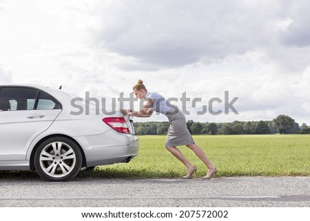 Full length side view of businesswoman pushing broken down car at countryside - stock photo